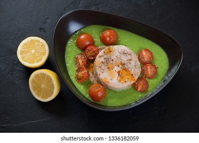 Black bowl with baked fish medallions, green peas puree, cherry tomatoes and lemon. Studio shot on a black stone background