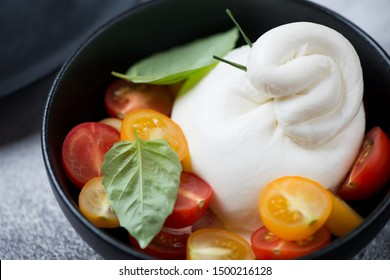 Black bowl with burrata cheese and cherry tomatoes, selective focus, close-up