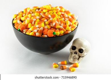 A black bowl over filled with Candy Corn taken on a white background.  A plastic toy skull is also shown in the photo