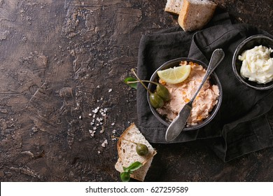 Black bowl of salmon pate with red caviar served with butter, sliced bread, capers, vintage knife and herbs on textile linen napkin over brown texture background. Top view.