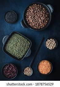 Black bowls of various dried legumes - beans, lentils, mungo beans and chickpeas on dark blue background. Overhead shot. Dark and moody.