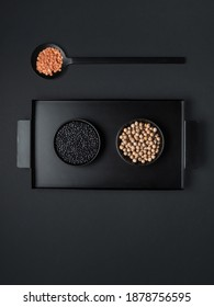 Black bowls of various dried legumes - beans, chickpeas and orange lentils on black tray and black background. Overhead shot with copy space.