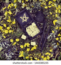 Black box with wooden runes and candles in flowers. Wicca, esoteric, divination and occult concept with magic objects for mystic rituals, Halloween, Beltane background