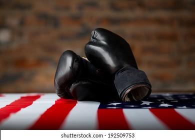 Black boxing gloves over american flag