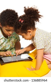 Black boy and girl playing with digital tablet computer and looks very busy
