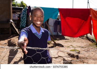 Black boy with his hand out to greet somebody and a huge smile on his face.