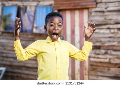 Black boy with his mouth open and hand in the air while standing infront of a shack