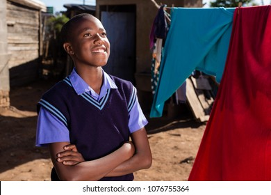 Black boy looking away with a smile on his facewhile in a township.