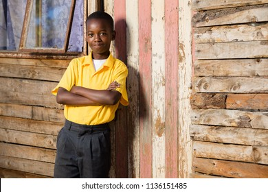 Black boy looking straight into the camera while his arms are crossed