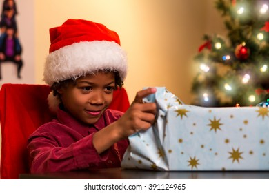 Black boy opening Christmas present. Kid opens present on Christmas. I wonder what's inside. Finally I can open it.