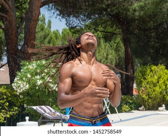 Black boy shakes wet dreadlocks to dry by the pool
