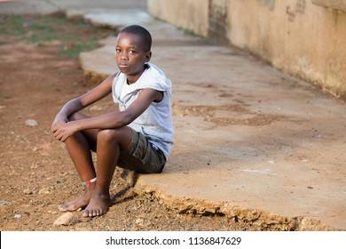 Black boy sitting down with a serious expression on his face