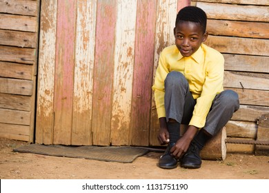 Black boy sitting down and tieing his shoes while looking into the camera