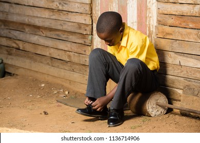 Black boy tieing his shoes while sitting in his school clothes