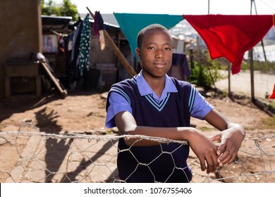 Black boy with a very serious expression standing against the fence in a township.