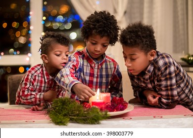 Black boys light Christmas candles. Children lighting red Christmas candles. Christmas eve at home. Happy holidays with brothers.