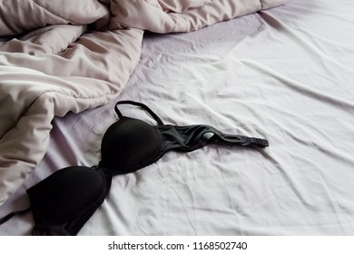 Black bra on rumbled bed with grey  blanket