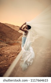 Black bride in long wedding dress stands and holds waving bridal veil in her hands on background of beautiful landscape and sky at sunset. Side view.