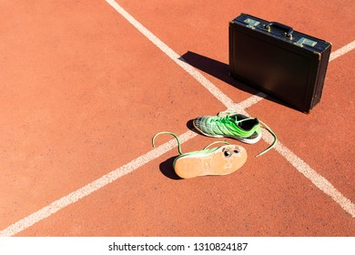 A black briefcase and a pair of broken green running shoes on a running track symbolizing competition, challenge and burnout in work and business.