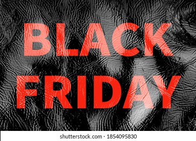 Black brilliant background patent leather texture close up, inscription black friday red letters.Black Friday pre-holiday shop and sale concept. Flyer shopping, online sale. Screensaver for the site.