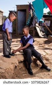 Black brother tieing his little brothers shoe in the township.