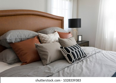 Black and brown pattern pillows setting on bed with brown leather headboard and table lamp