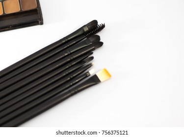 Black brushes are placed on a table in a white background.