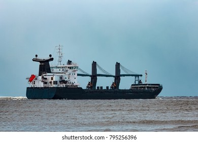 Black bulk carrier sailing to the sea in cold winter