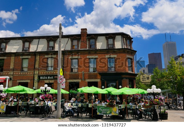 Black Bull tavern at lunch time on Queen street with financial towers Toronto, Ontario, Canada - June 12, 2009