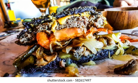 Black Burger with cheddar cheese, mushrooms and pickle. (cut half burger)