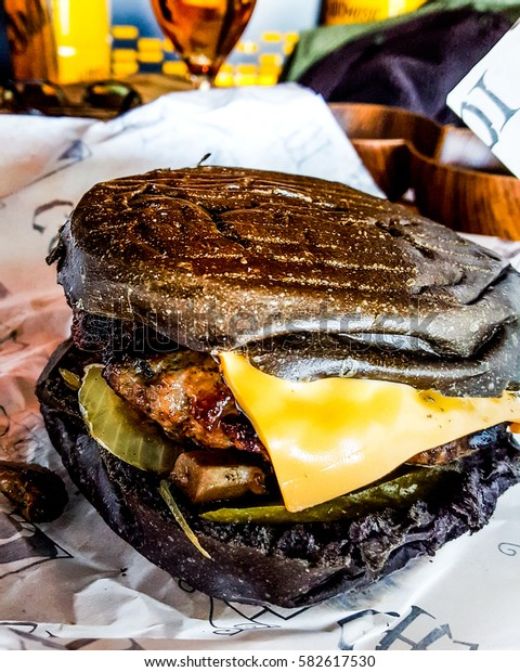 Black Burger with cheddar cheese, mushrooms and pickle.