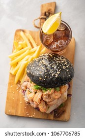 Black burger with fish and shrimps. Fishburger with prawns. Top view.