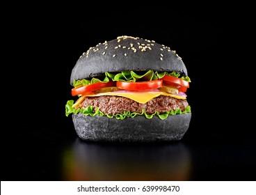 Black burger isolated on black background.