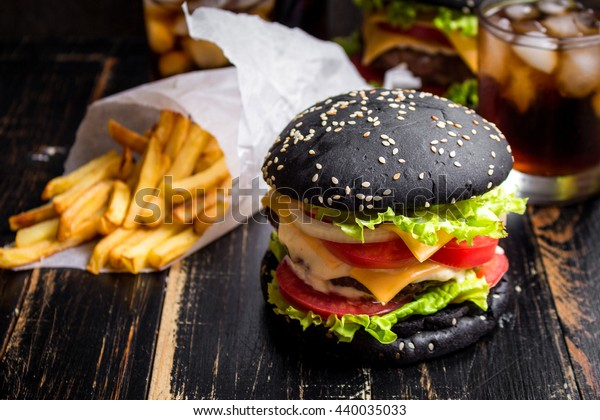 Black burger with meat patty, cheese, tomatoes, mayonnaise, french fries in a paper cup and glass of cold cola soda with ice. Dark wooden rustic table. Modern fast food lunch