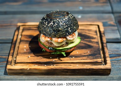 Black burger with prawns on wooden board