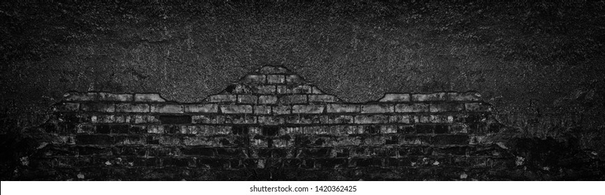 Black burnt brick wall with fallen off plaster wide texture. Crumbled old shabby brickwork. Dark gloomy large background