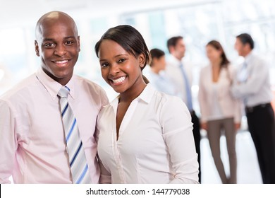 Black business couple looking happy at the office
