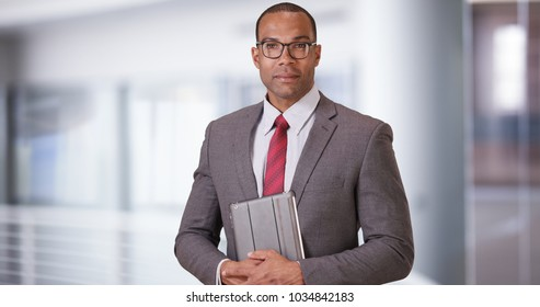 A black business professional poses for a portrait with his tablet and glasses