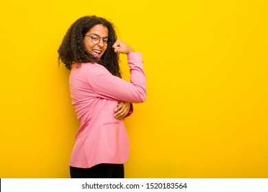 black business woman feeling happy, satisfied and powerful, flexing fit and muscular biceps, looking strong after the gym against orange wall