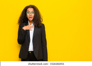 black business woman feeling shocked, astonished and surprised, with hand on chest and open mouth, saying who, me? against orange wall