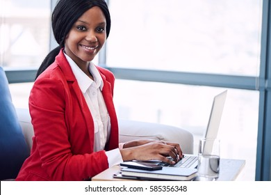 Black business woman looking at camera while smiling, with her hands still on the keyboard of her laptop computer where she was sitting working before looking up at camera.