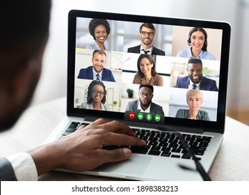 Black Businessman Having Online Business Meeting With Colleagues Making Video Call On Laptop Sitting In Modern Office. Coworkers Communicating Via Video Conference. Distance Work Communication