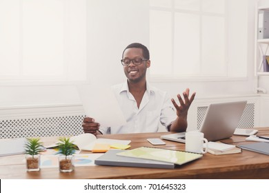 Black businessman read documents in modern white office. Young man with papers, copy space