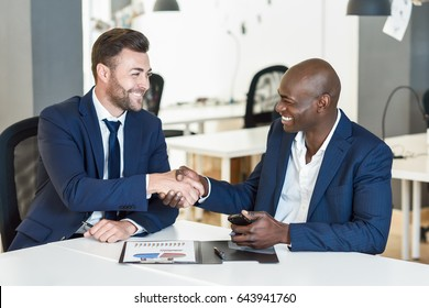 Black businessman shaking hands with a caucasian one wearing suit in a office. Two smiling men wearing blue suits working in an office with white furniture