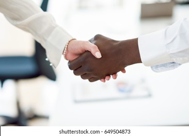 Black businessman shaking hands with a caucasian businesswoman wearing suit in a office. Close-up shot