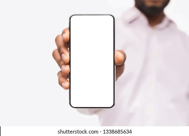 Black businessman showing smartphone with blank screen, isolated on white background, copy space