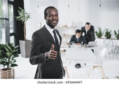black businessman showing thumb up with blurred colleagues on background