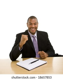 A black businessman sitting at a desk with a pen and pad with triumphant look on his face
