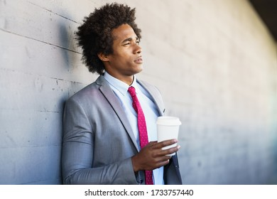 Black Businessman taking a coffee break with a take-away glass. Man with afro hair.