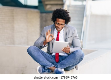 Black Businessman using a digital tablet sitting near an office building. Man with afro hair.